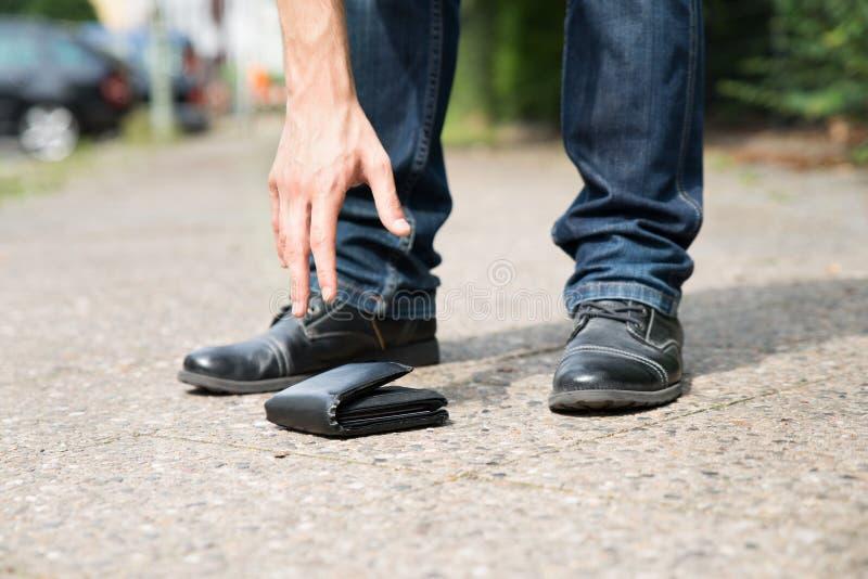 Homem que escolhe a carteira acima caída imagem de stock