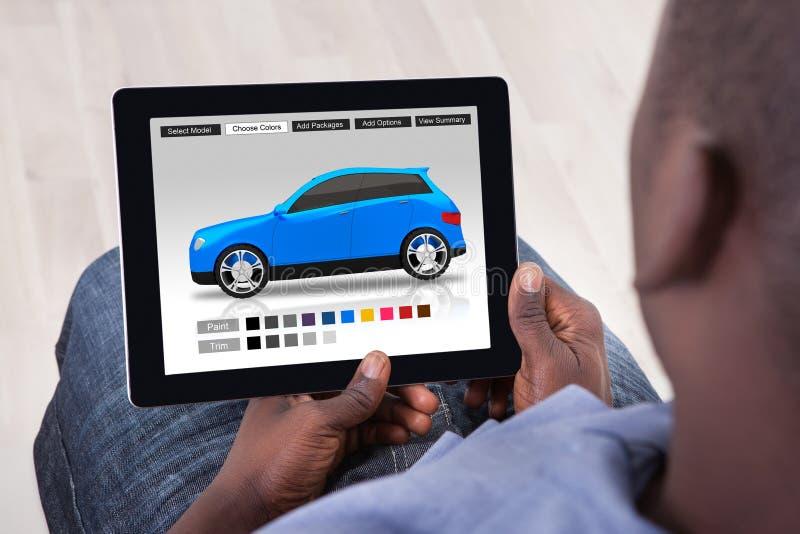 Homem que escolhe a cor do carro na tabuleta de Digitas foto de stock royalty free