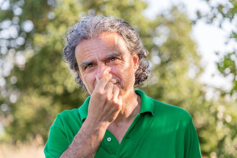 Homem que escolhe seu nariz fotografia de stock