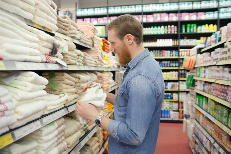 Homem que escolhe toalhas no supermercado fotografia de stock