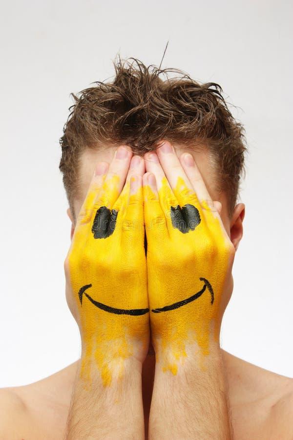 Homem que esconde sua face sob a máscara do sorriso fotografia de stock