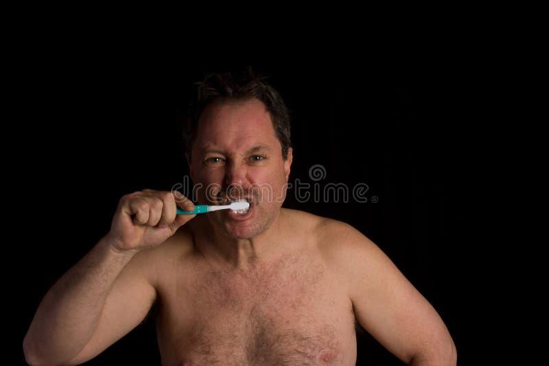 Homem que escova seus dentes imagens de stock royalty free