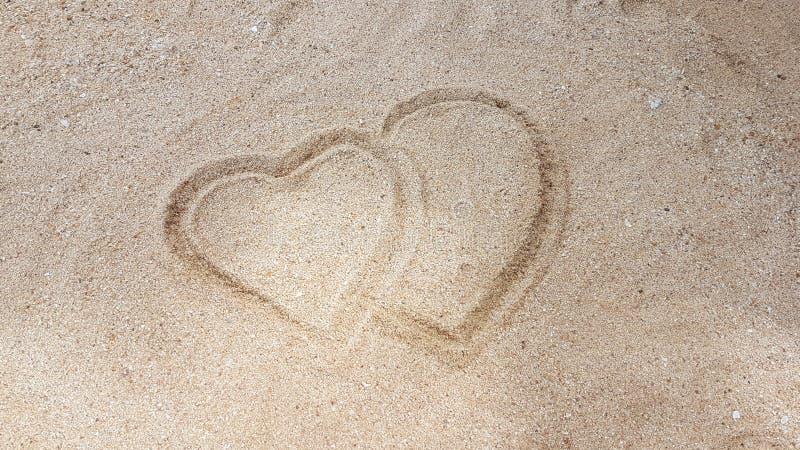 Homem que escreve o coração na areia dourada fotos de stock royalty free