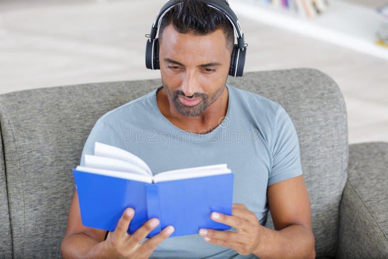 Homem que escuta o audiobook atrav?s dos fones de ouvido fotos de stock