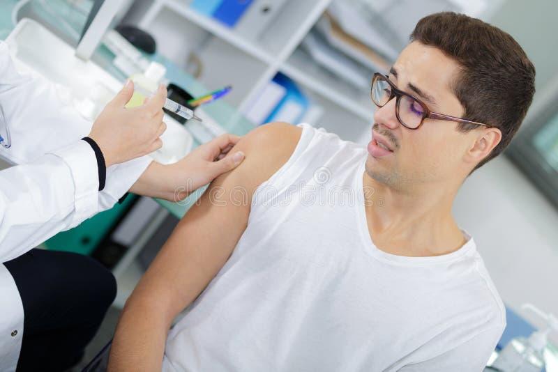 Homem que espera nervosamente a injeção no braço foto de stock
