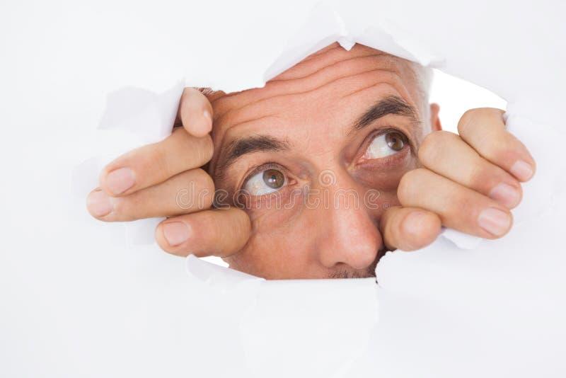 Homem que espreita através da superfície rasgada do branco imagem de stock