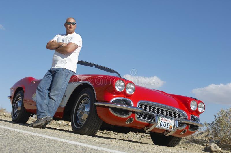 Homem que está ao lado do carro clássico na estrada fotos de stock