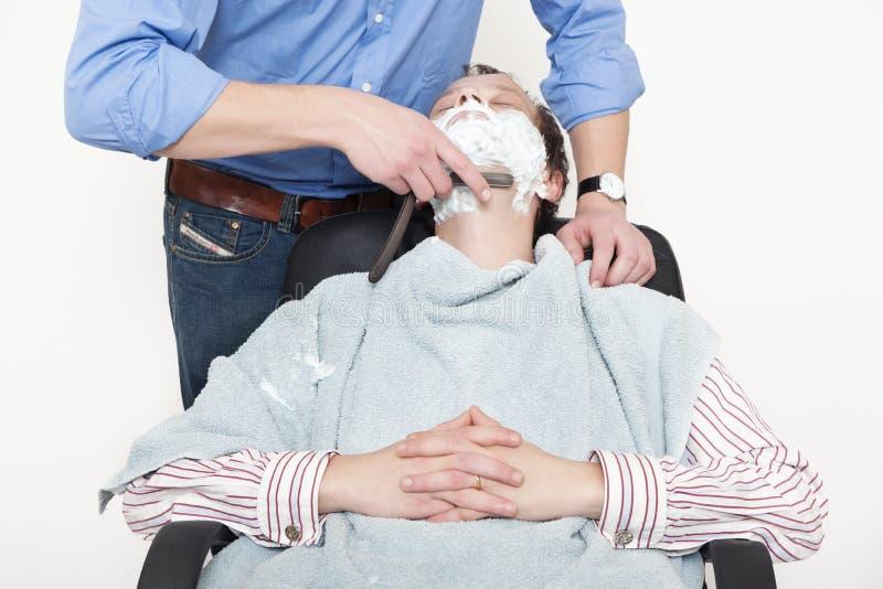 Homem que está sendo raspado com a lâmina cortada da garganta fotografia de stock