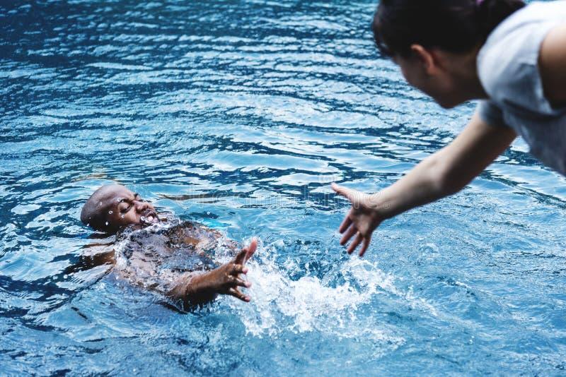 Homem que está sendo salvado da água foto de stock royalty free