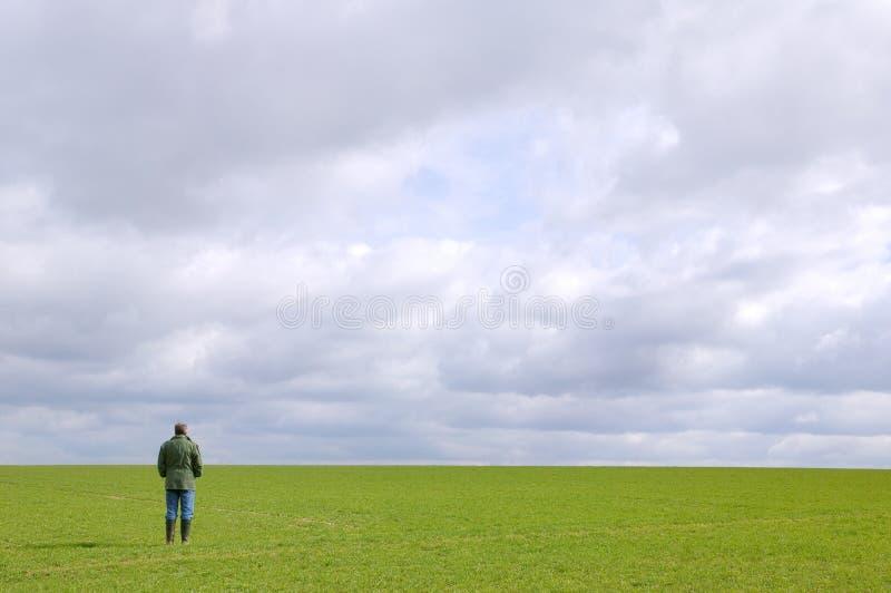 Homem que está sozinho em um campo foto de stock royalty free