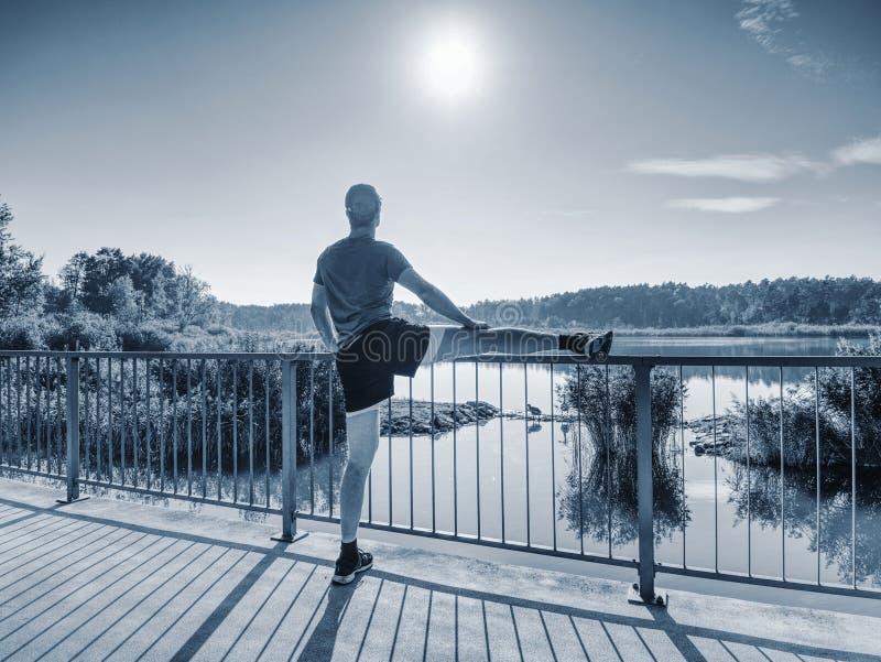 Homem que estica os pés antes da parte externa corrida dentro da manhã ensolarada fotos de stock royalty free