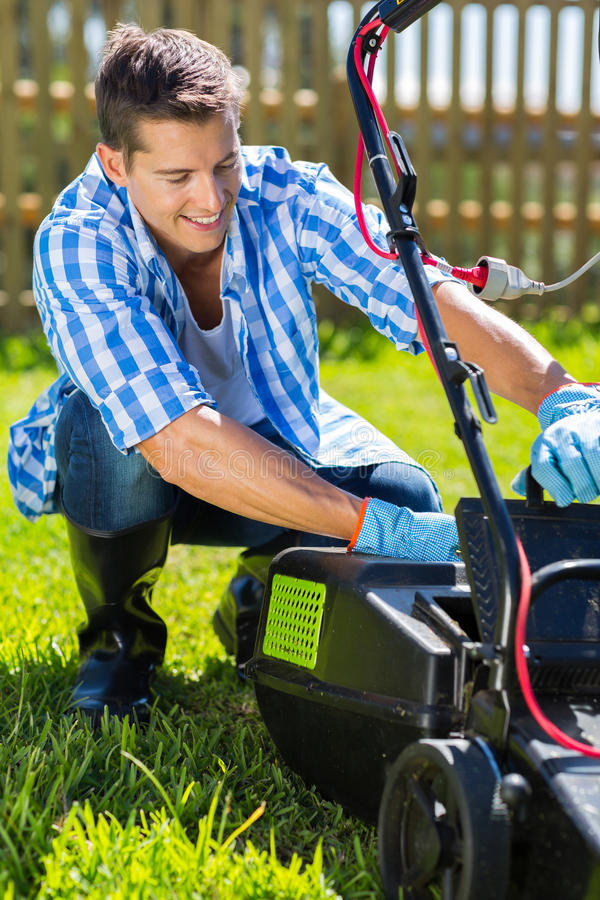Homem que esvazia o coletor da grama do lawnmower fotografia de stock royalty free