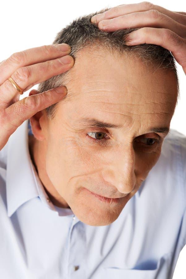 Homem que examina seu cabelo foto de stock royalty free