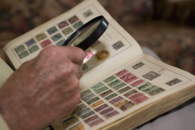 Homem que examina um livro de selo velho imagens de stock royalty free