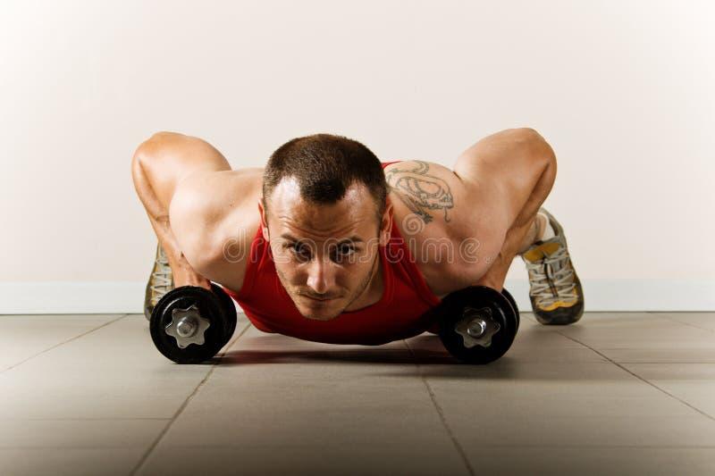 Homem que exercita com dumbbells fotografia de stock