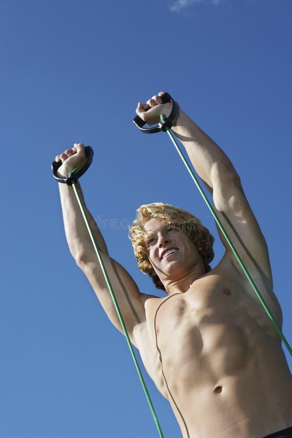 Homem que exercita contra o céu azul fotos de stock