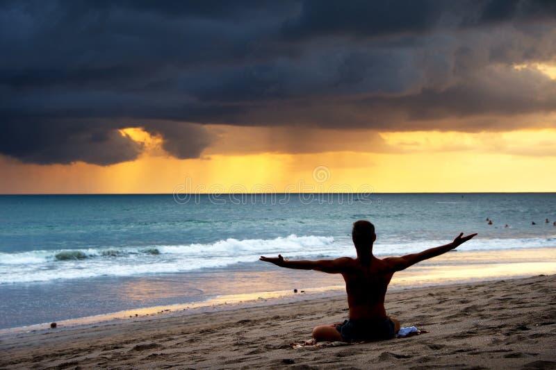 Homem que exercita a ioga Bali, praia imagem de stock royalty free
