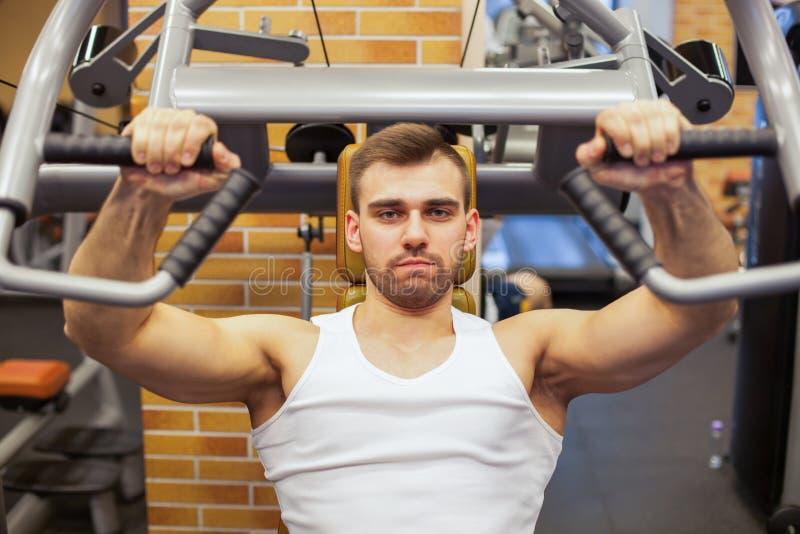 Homem que exercita na ginástica O atleta da aptidão que faz a caixa exercita na máquina vertical da imprensa de banco foto de stock