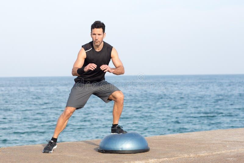 Homem que exercita na plataforma do equilíbrio imagem de stock royalty free