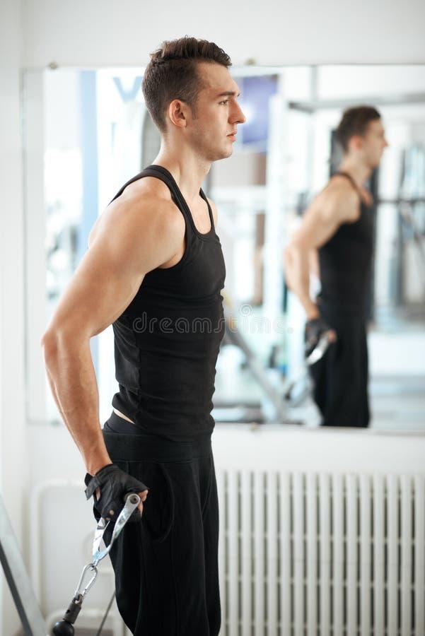 Homem que exercita no instrutor para os músculos do tríceps fotos de stock