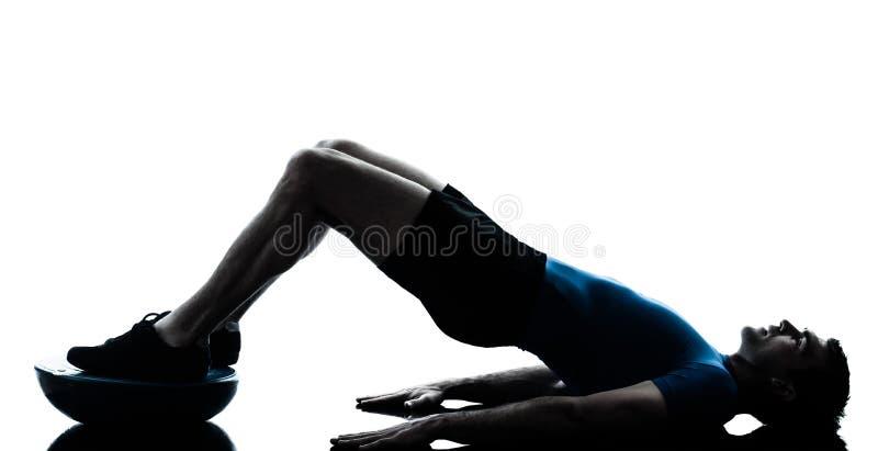 Homem que exercita a postura da aptidão do exercício do bosu fotos de stock