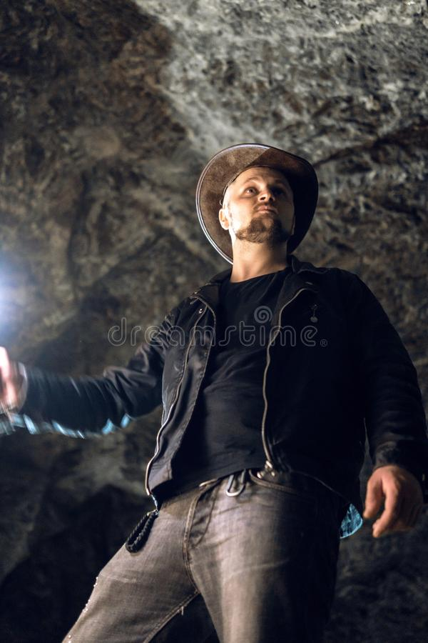 Homem que explora a caverna enorme Os viajantes da aventura vestiram o chapéu de vaqueiro e a trouxa, casaco de cabedal extremo,  imagem de stock royalty free