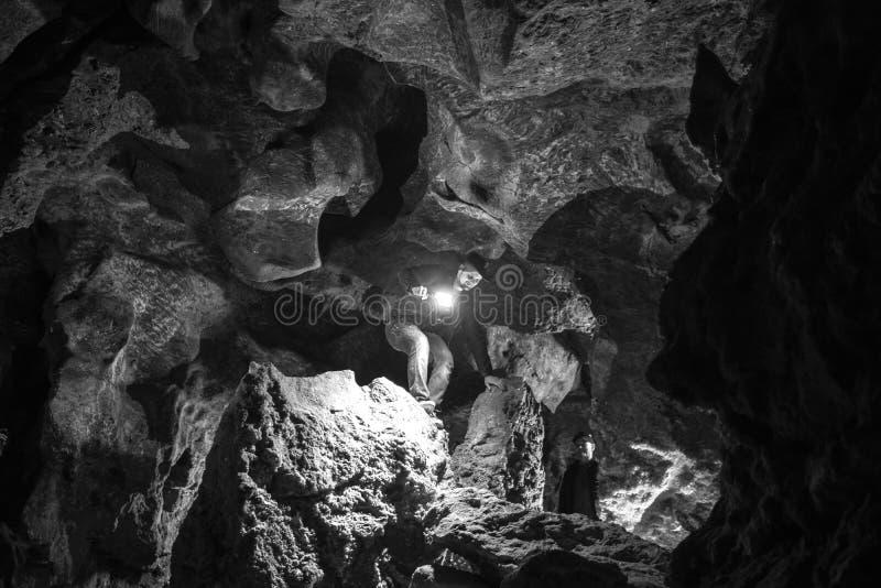 Homem que explora a caverna enorme Os viajantes da aventura vestiram o chapéu de vaqueiro e a trouxa, casaco de cabedal preto e b imagem de stock royalty free