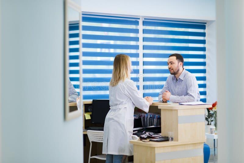 Homem que fala ao recepcionista fêmea no hospital imagens de stock
