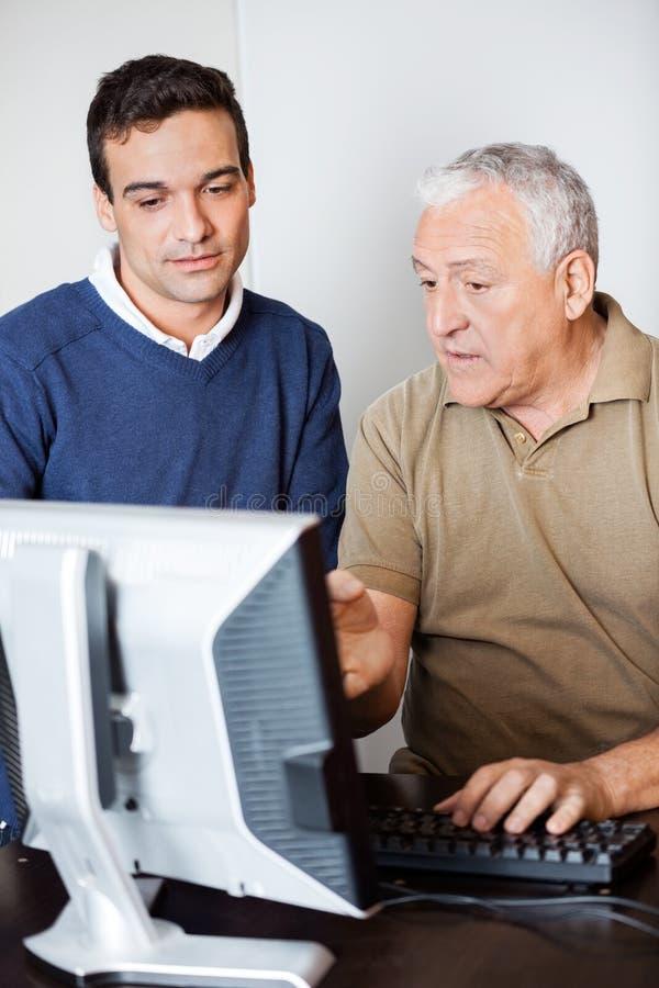 Homem que fala com o monitor do computador de While Pointing Towards do professor fotografia de stock