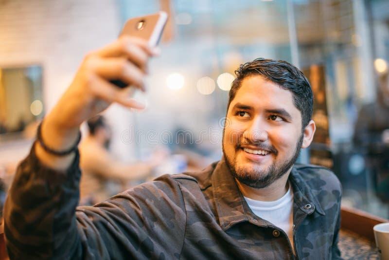 Homem que fala a conversação em linha usando o telefone celular Indivíduo latin de sorriso moderno imagens de stock