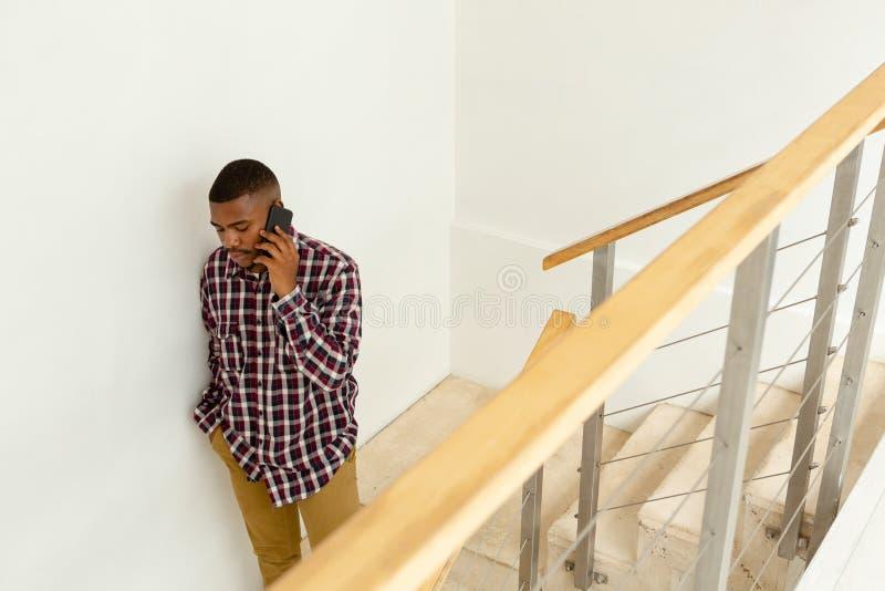 Homem que fala no móbil em escadas em uma casa confortável imagens de stock royalty free