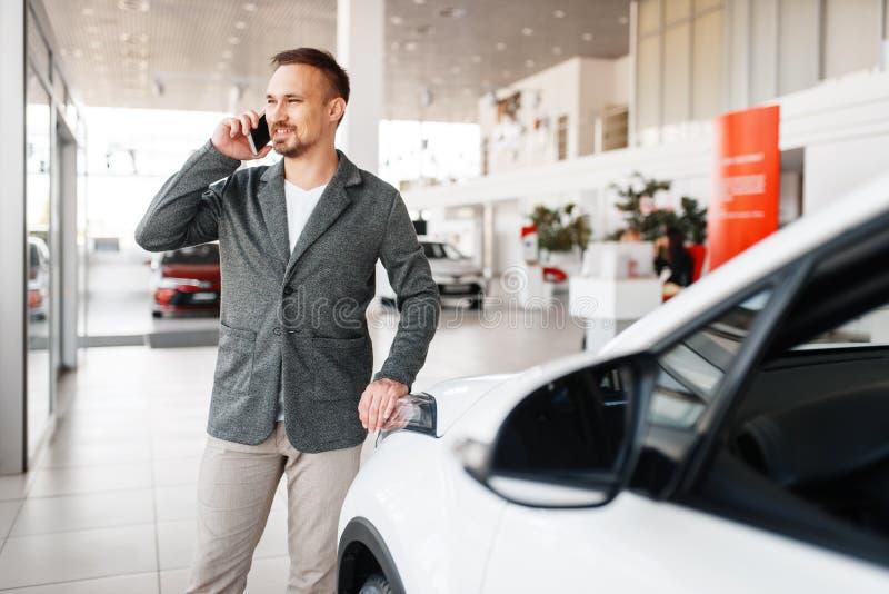 Homem que fala pelo telefone perto do carro novo na sala de exposições fotografia de stock