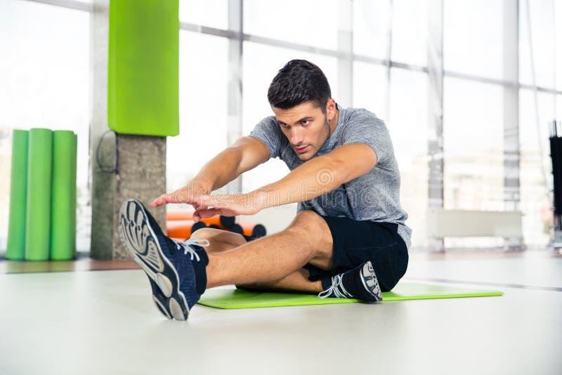 Homem que faz esticando exercícios no gym fotos de stock