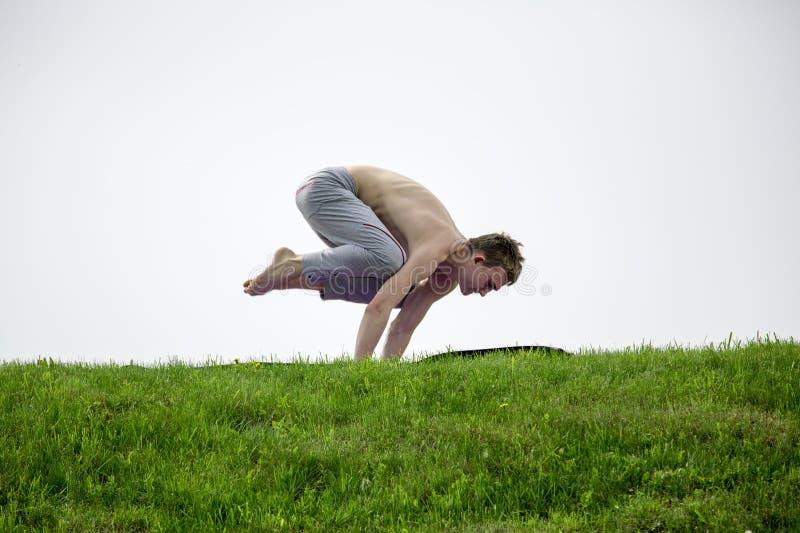 Homem que faz exercícios da ioga no parque fotografia de stock royalty free