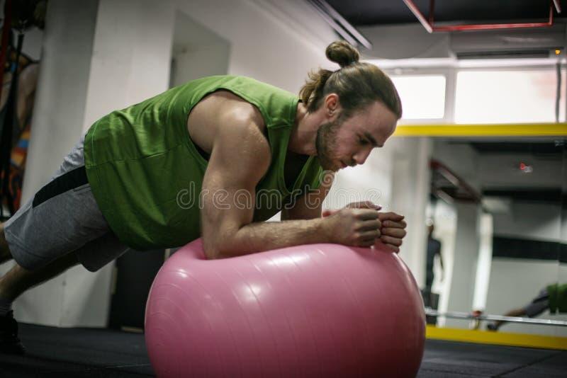 Homem que faz exercícios do equilíbrio com bola do ajuste imagens de stock