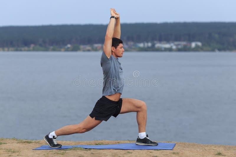 Homem que faz a ioga exterior Exercício praticando da aptidão da ioga do homem novo exterior no mar bonito imagens de stock