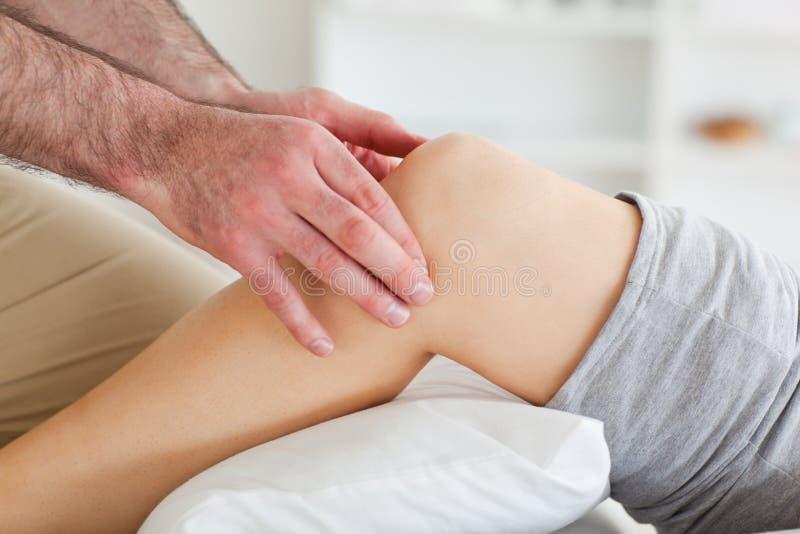 Homem que faz massagens o joelho de uma mulher de encontro fotos de stock