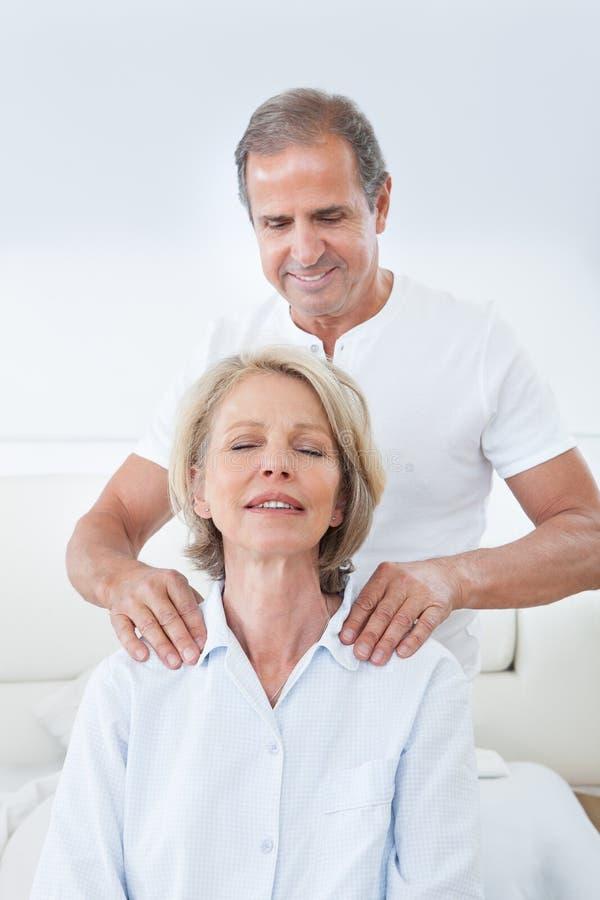 Homem que faz massagens o ombro da mulher fotos de stock