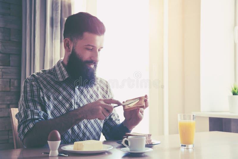 homem que faz o café da manhã com xícara de café e brindes fotos de stock