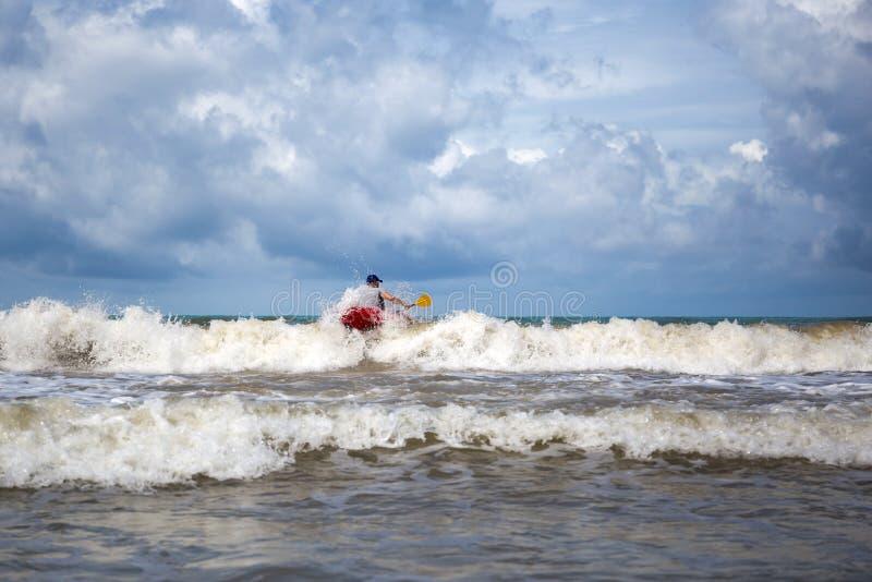 Homem que faz o caiaque que surfa no mar imagem de stock royalty free