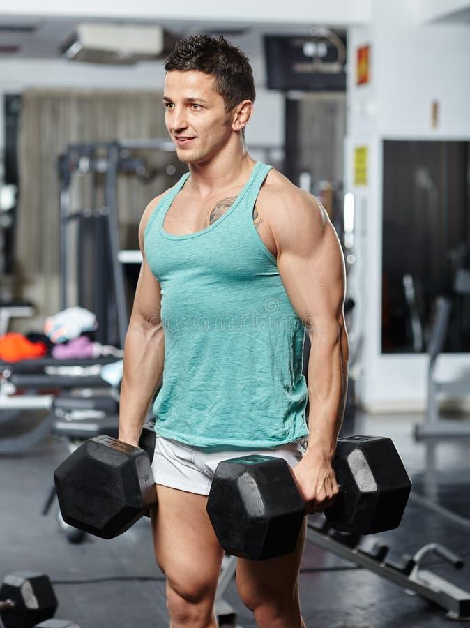 Homem que faz o exercício com pesos pesados imagem de stock royalty free