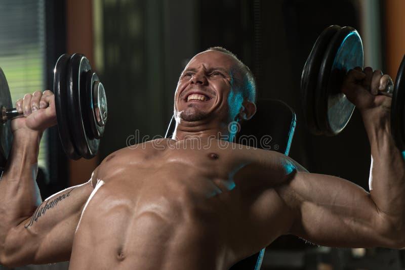 Homem que faz o exercício da imprensa de banco do declive do peso imagens de stock