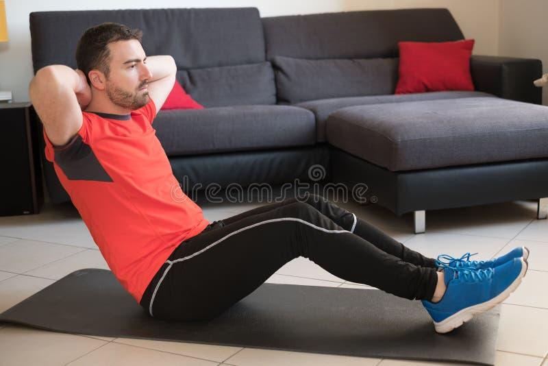 Homem que faz o exercício do corpo e que dá certo em casa fotos de stock royalty free