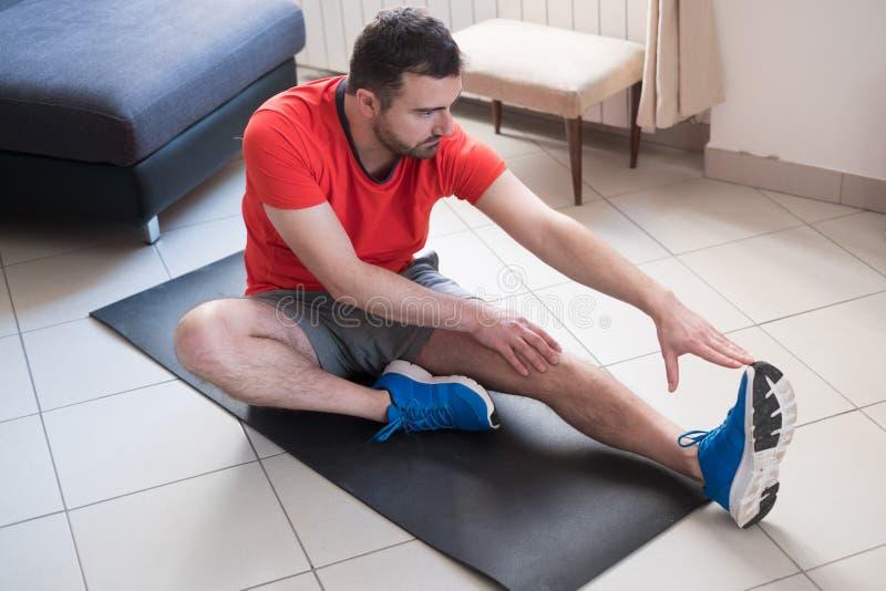Homem que faz o exercício do corpo e que dá certo em casa fotografia de stock