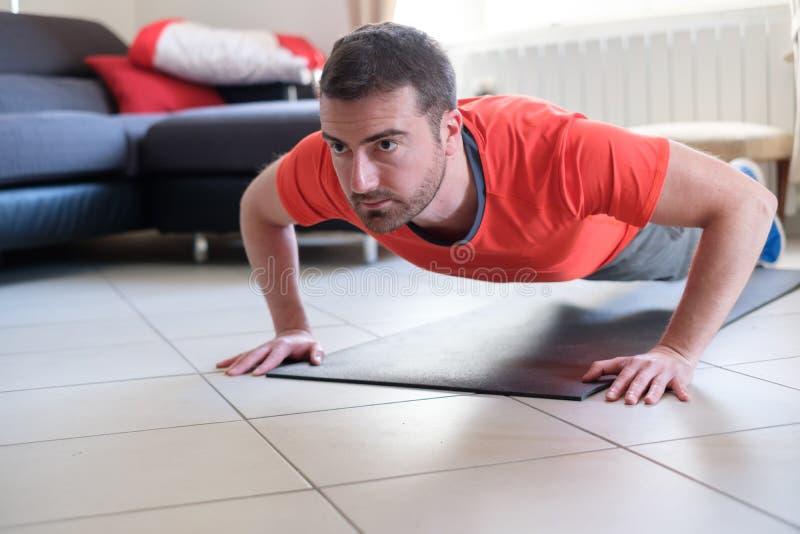 Homem que faz o exercício do corpo e que dá certo em casa fotografia de stock royalty free