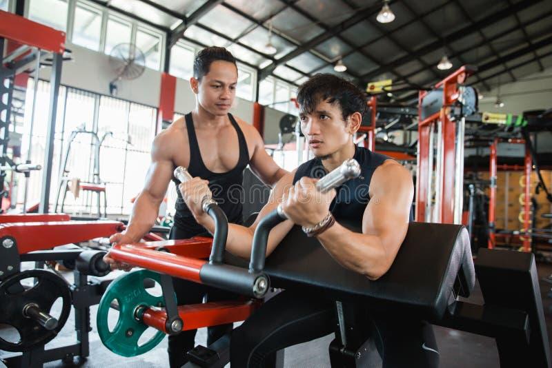 Homem que faz o exercício para o bíceps com instrutor fotografia de stock royalty free