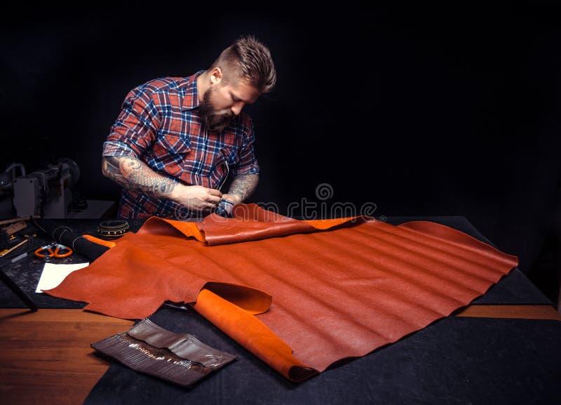 Homem que faz o saco com couro imagens de stock