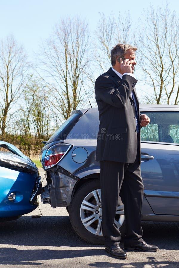 Homem que faz o telefonema após o acidente de tráfico imagem de stock