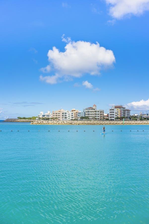 Homem que faz a pá que surfa no porto de pesca de Hamakawa à proximidade da vila americana na cidade de Chatan de Okinawa imagem de stock