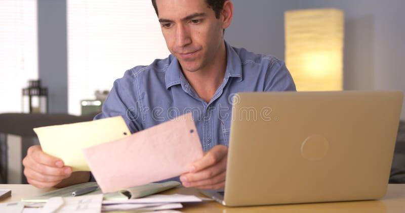 Homem que faz seus impostos na mesa imagens de stock